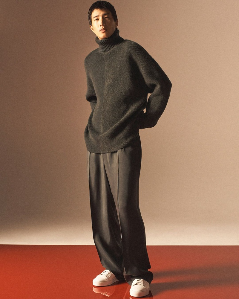 Nathaniel Dam sports an oversized turtleneck sweater with relaxed trousers for COS' holiday 2020 men's campaign.