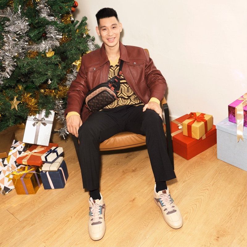 Sitting for a photo, Jeremy Lin rocks a Coach belt bag for the brand's holiday 2020 campaign.