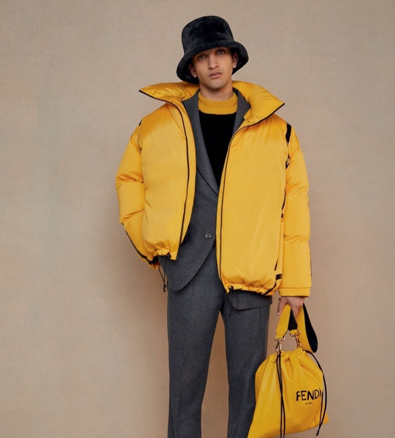 Noah Sapon dons a yellow puffer jacket over a gray suit from Fendi's fall-winter 2020 collection.