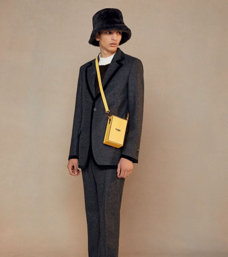 A chic vision, Jethro Sapon models a gray suit with black piping, finished with a bucket hat and yellow leather bag.