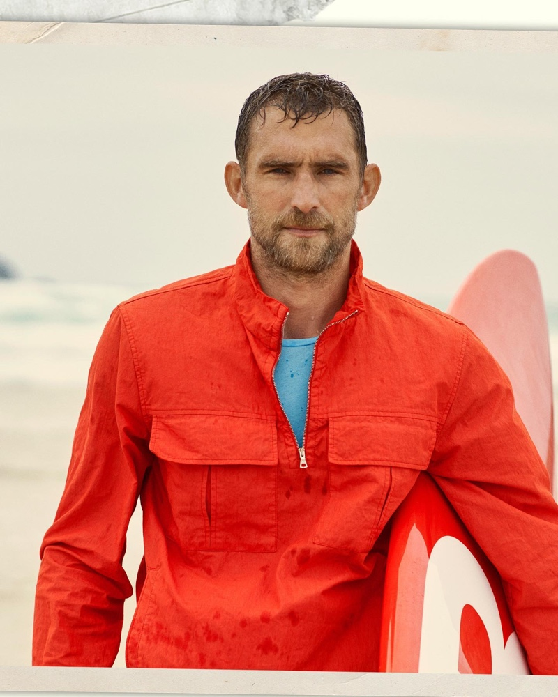 British model Will Chalker dons a rescue red smock jacket by Orlebar Brown.