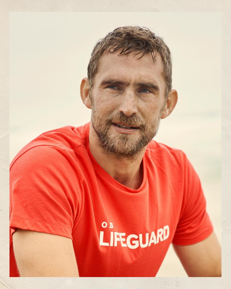 Front and center, Will Chalker models a rescue red lifeguard slogan t-shirt.