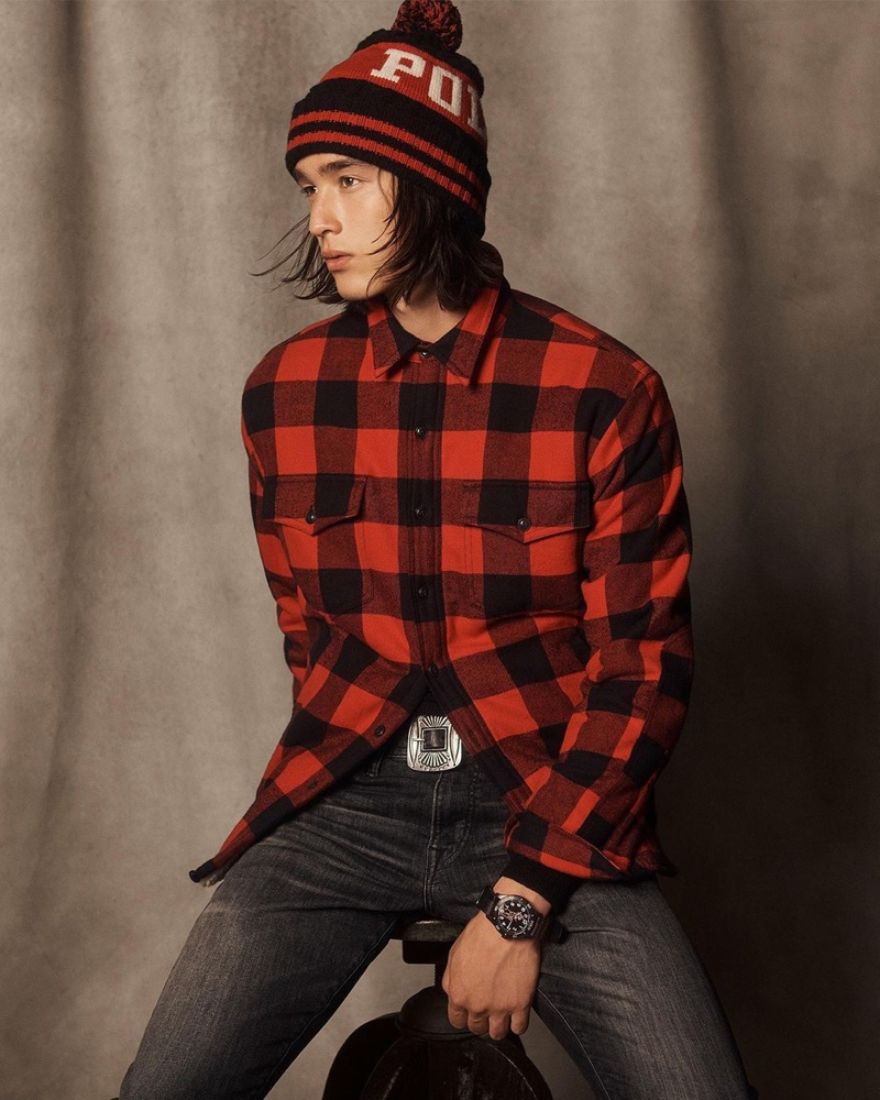 Peter Meyer dons a red and black buffalo check shirt with a knit pom beanie and distressed jeans from POLO Ralph Lauren's holiday 2020 collection.