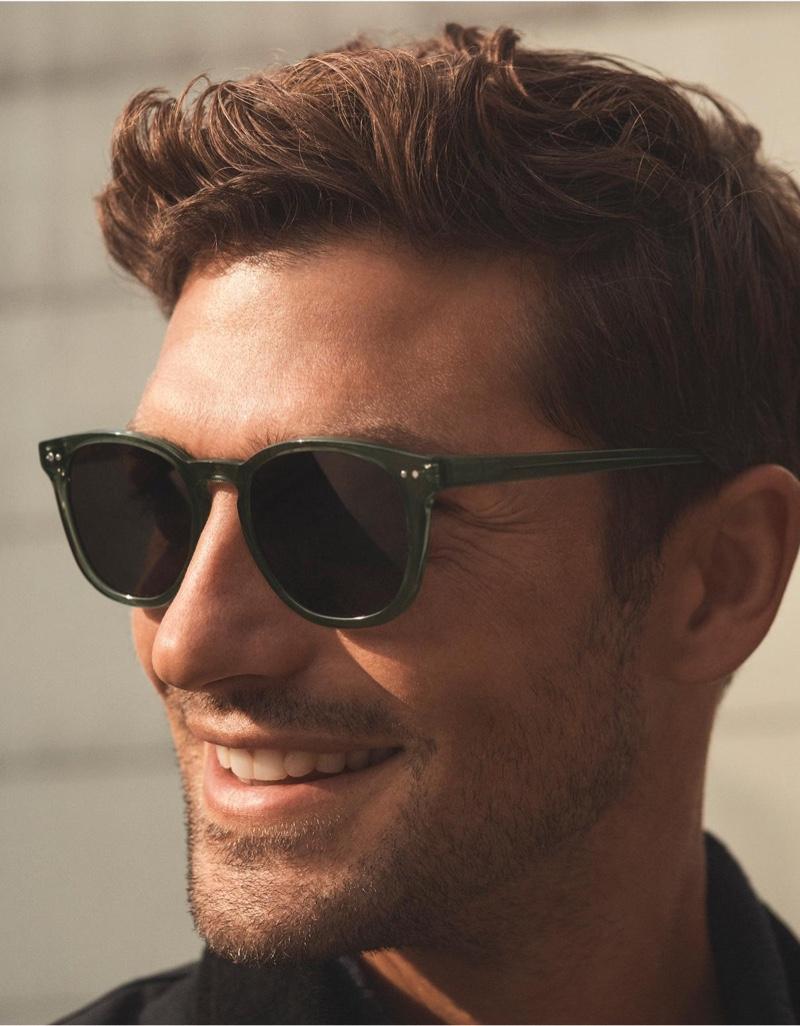 Model Benj Lee is all smiles in Warby Parker's Toddy sunglasses in seaweed crystal.