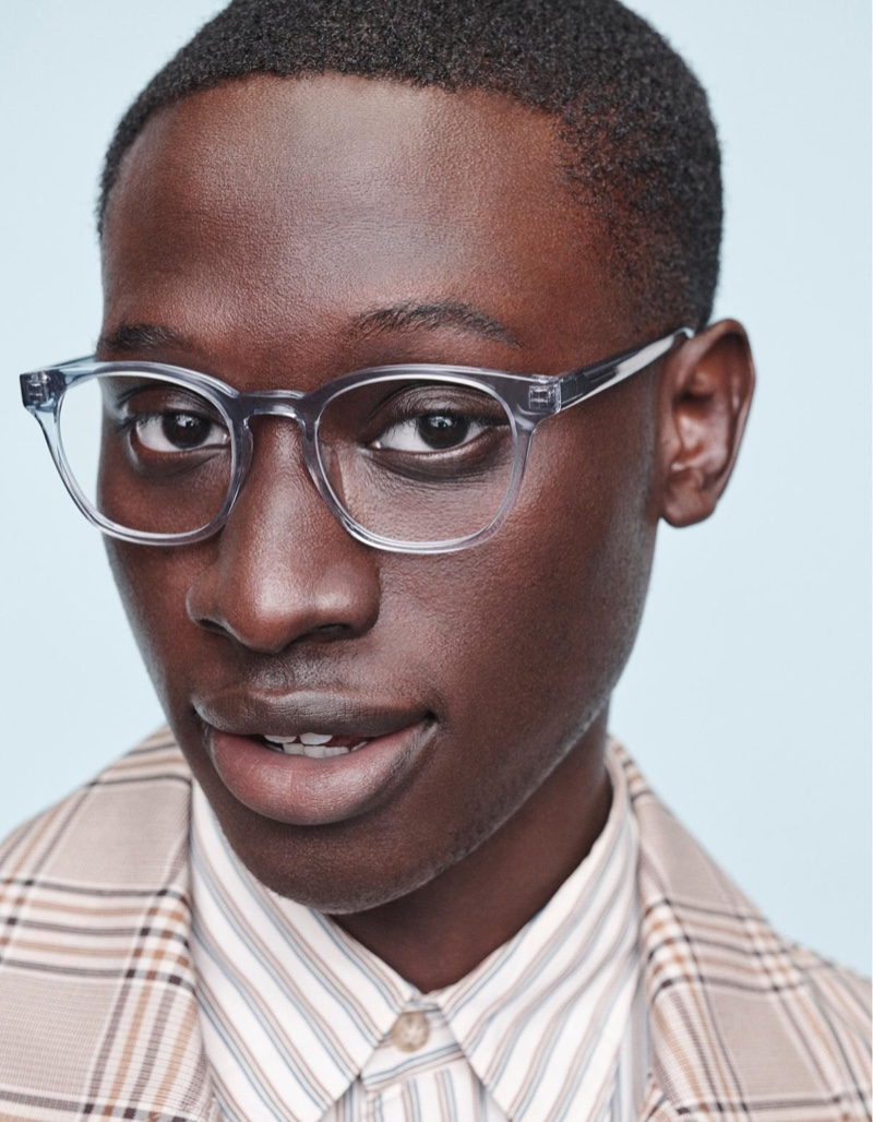 Front and center, Baba Diop models Warby Parker's Felix glasses with a low bridge fit in pacific crystal.