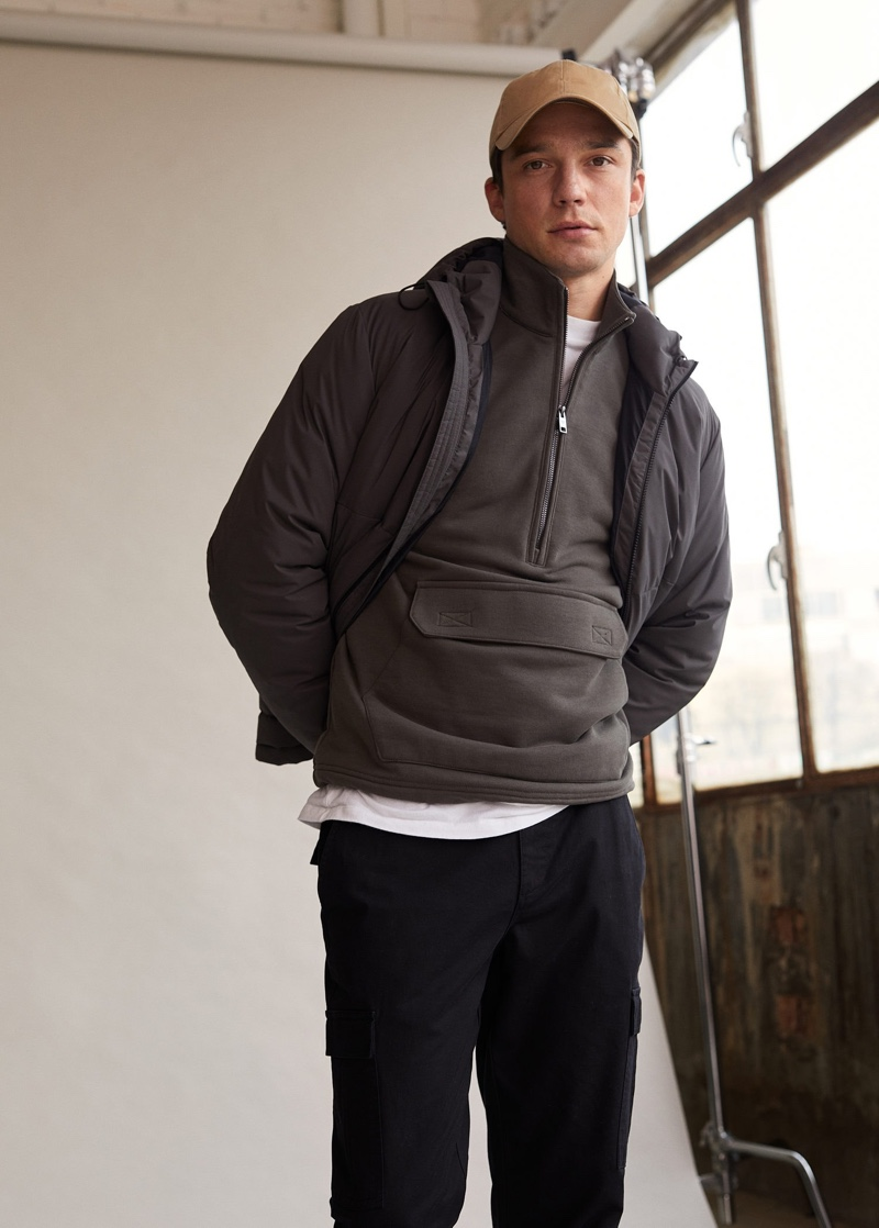 Layering for a cool day, Alexis Petit wears a half-zip pullover with a jacket and cargo pants from Mango Man.
