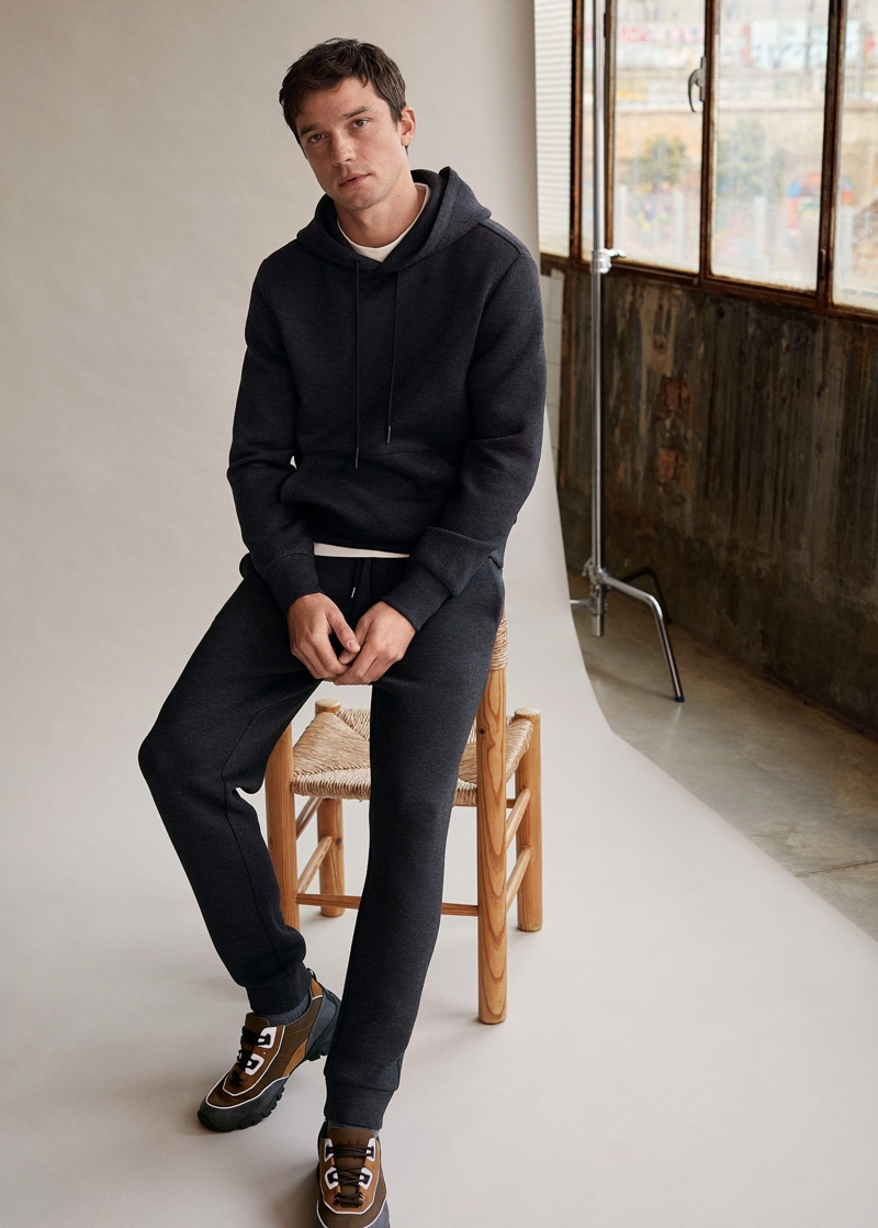 Embracing laid-back style, Alexis Petit models a matching hoodie and joggers from Mango Man.