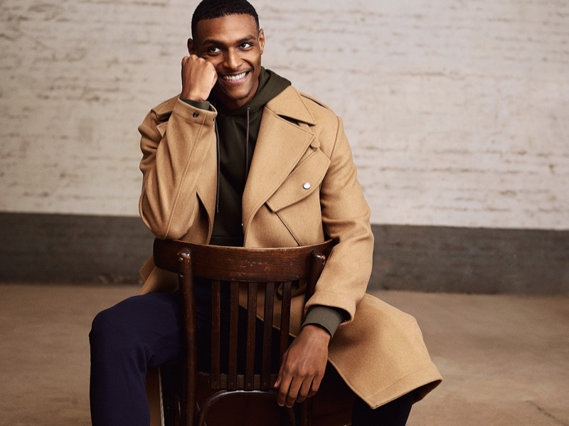 All smiles, Shawn Golomingi sports a camel-colored coat from BOSS.