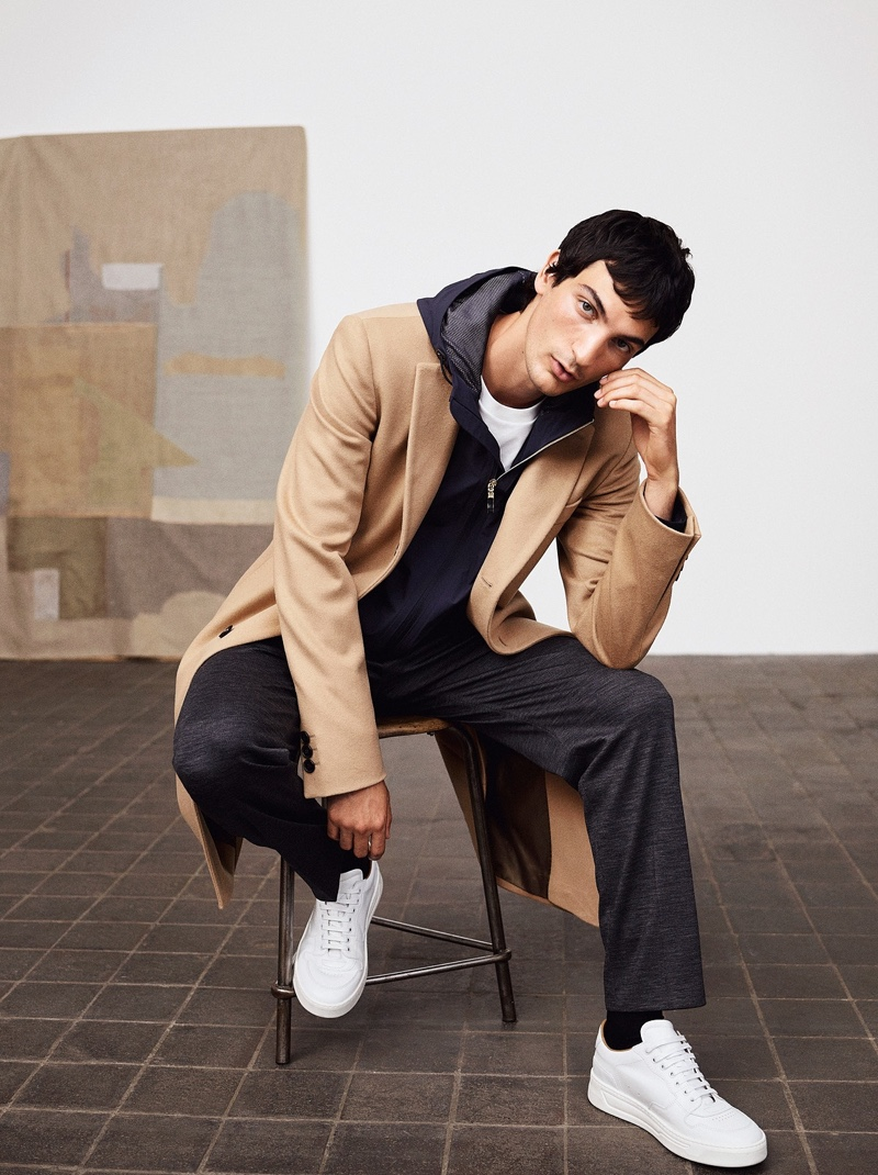 Sitting for a portrait, Luca Lemaire wears a BOSS camel coat with full-zip hooded jacket and pants.