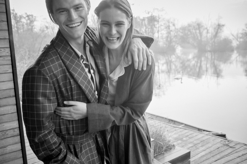 All smiles, Oliver Cheshire wears a men's navy check tasseled belt robe from Derek Rose in pure wool.