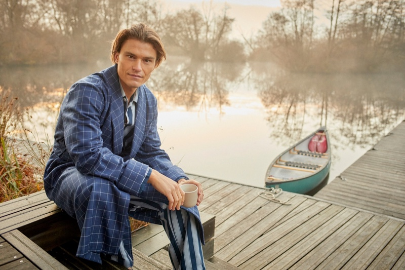 Connecting with Derek Rose for the season, Oliver Cheshire dons a men's navy check tasseled belt robe in pure wool with a striped pajama set.