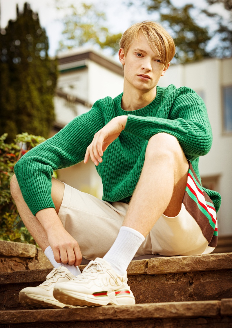 Fynn wears sweater, shorts, and sneakers Gucci.