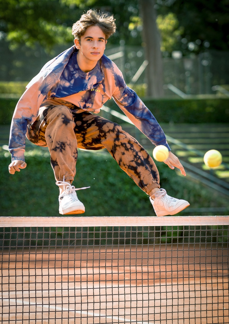 Luis wears tie-dye sweatshirt Diesel, pants iets frans, and sneakers Nike.
