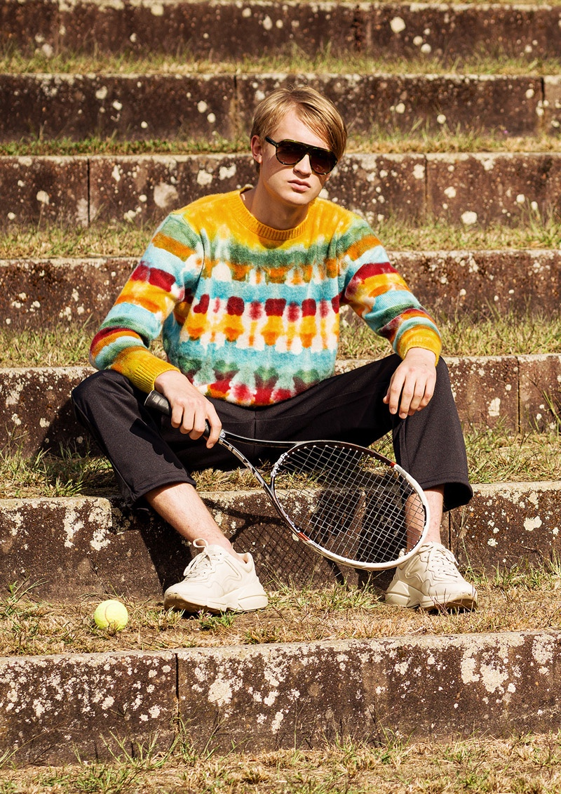 Fynn wears sweater The Elder Statesman, pants Fred Perry, and sneakers Gucci.