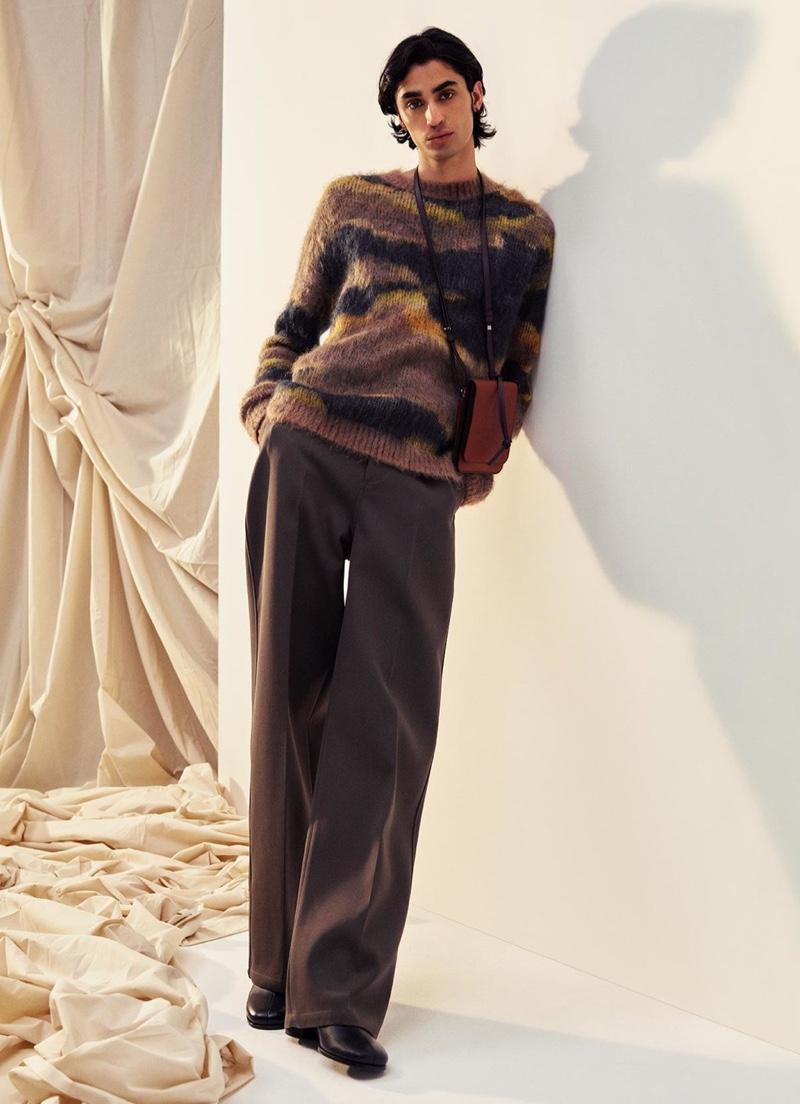 Aramish Mangi dons an Acne Studios sweater with Bottega Veneta trousers, a Loewe bag, and Maison Margiela shoes.