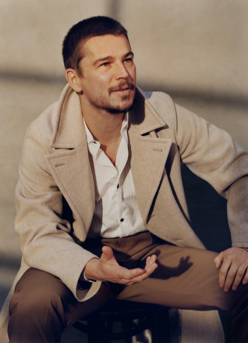 Sitting for a photo, Josh Hartnett sports an Auralee wool coat, Mr P shirt, and Brioni trousers.