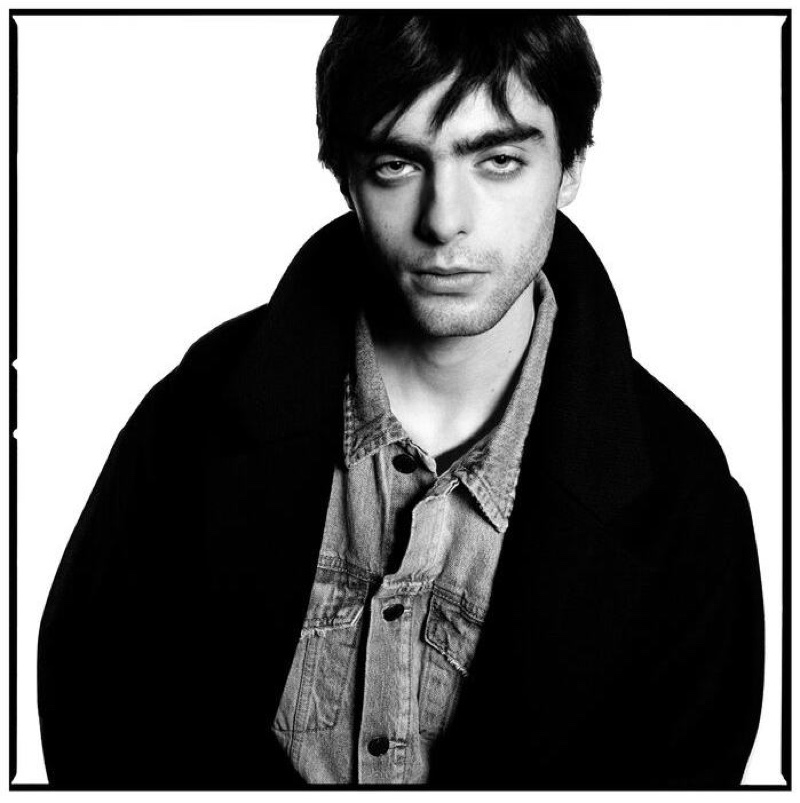 Appearing in a black and white portrait, Lennon Gallagher wears an oversized coat and light wash denim jean jacket from Zara Man.