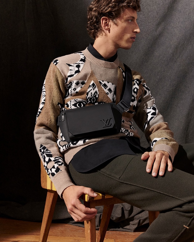 Sitting for a photo, Alexis Maçon-Dauxerre dons a leather sling bag from Louis Vuitton's new LV Aerogram collection.