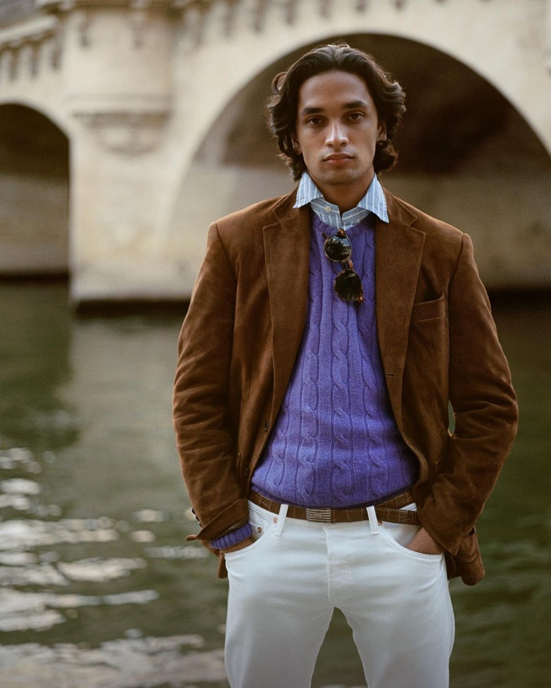 Model Sanjay Apavou dons a purple cable-knit sweater with a striped oxford shirt, brown suede jacket, and white pants from POLO Ralph Lauren.