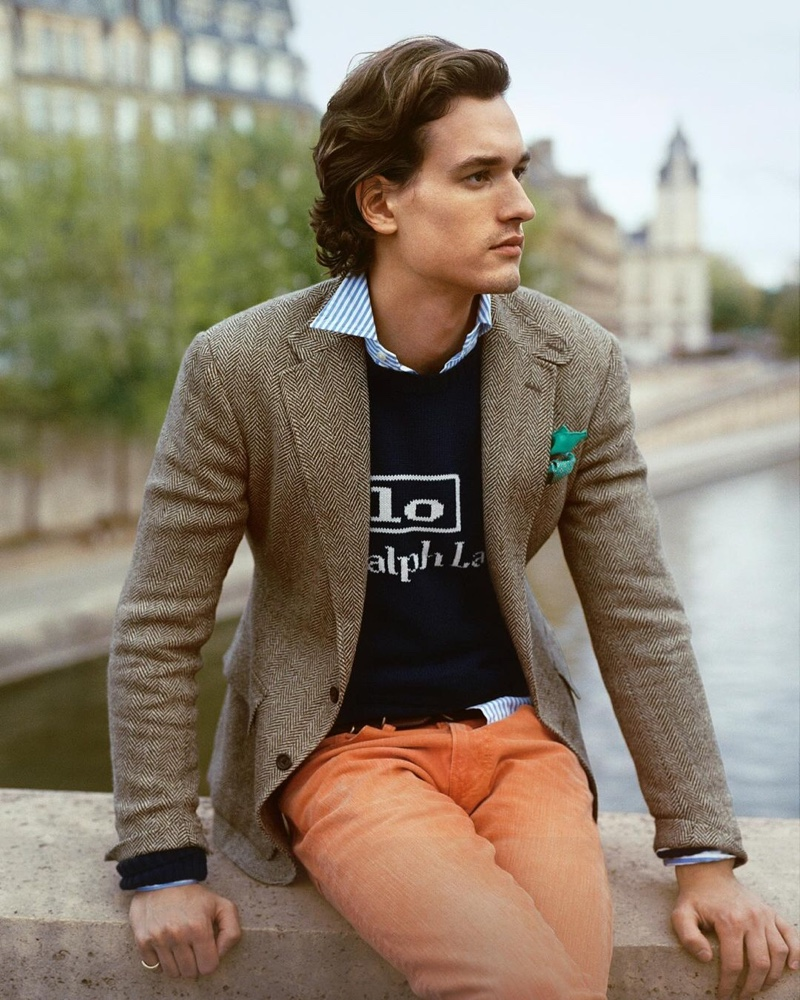 A regular face of POLO Ralph Lauren, Jegor Venned wears orange jeans with a logo knit sweater, tweed blazer, and striped oxford shirt.