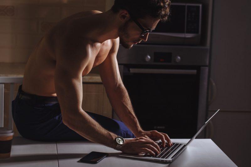 Shirtless Model Wearing Glasses on Laptop