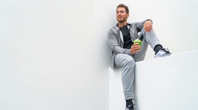 Sitting Man Grey Sweatpants Hoodie Drinking Smoothie