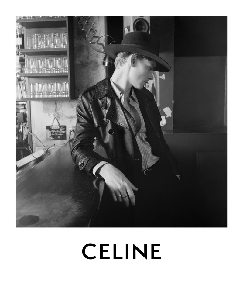 A chic vision, Thomas Brodie-Sangster sports a classic fedora and leather trench coat for Celine's spring-summer 2021 campaign.