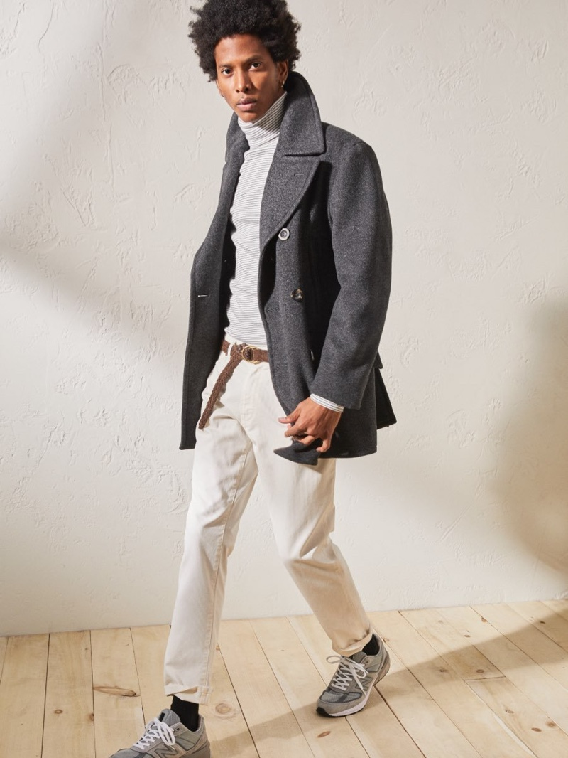 Keeping warm, Rafael Mieses wears a Todd Snyder + Private White Manchester wool cashmere peacoat in charcoal with a Todd Snyder jersey stripe turtleneck in white and New Balance Made in USA 990V5 sneakers in grey.