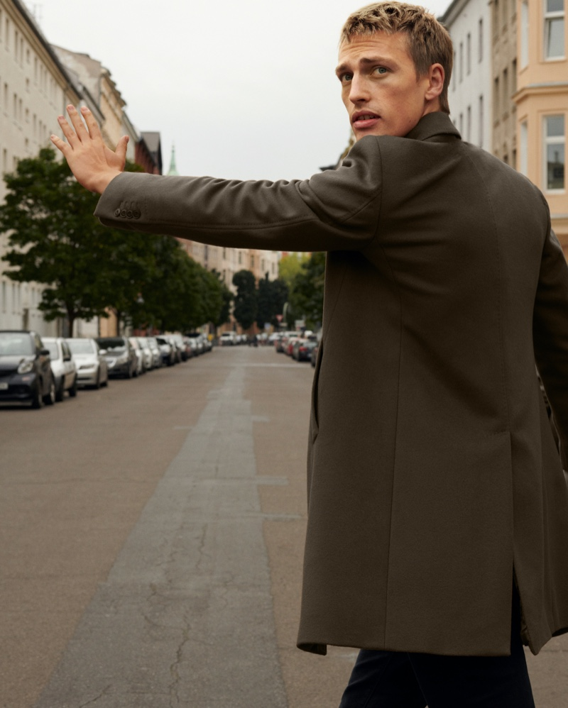 Hailing a taxi, Victor Nylander dons a sharp coat from Massimo Dutti.