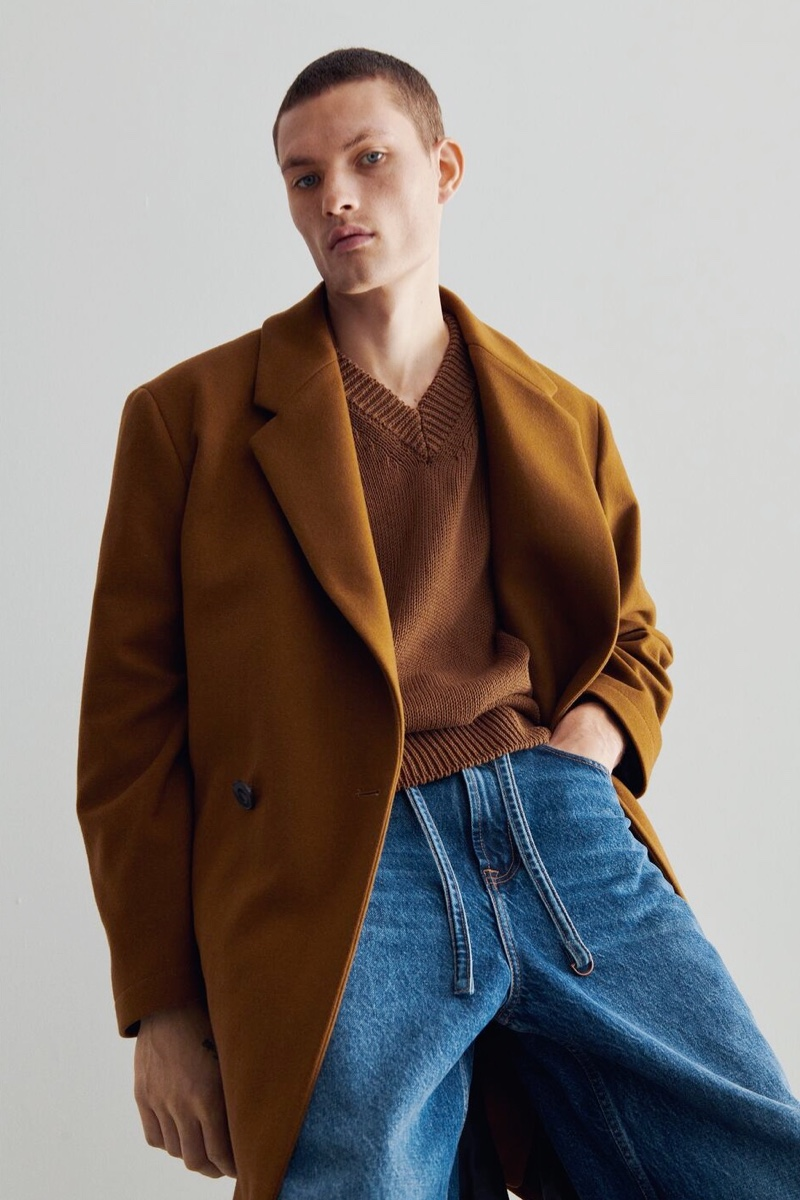 William Los dons a relaxed fit double-breasted coat with a v-neck sweater and jeans from Zara.