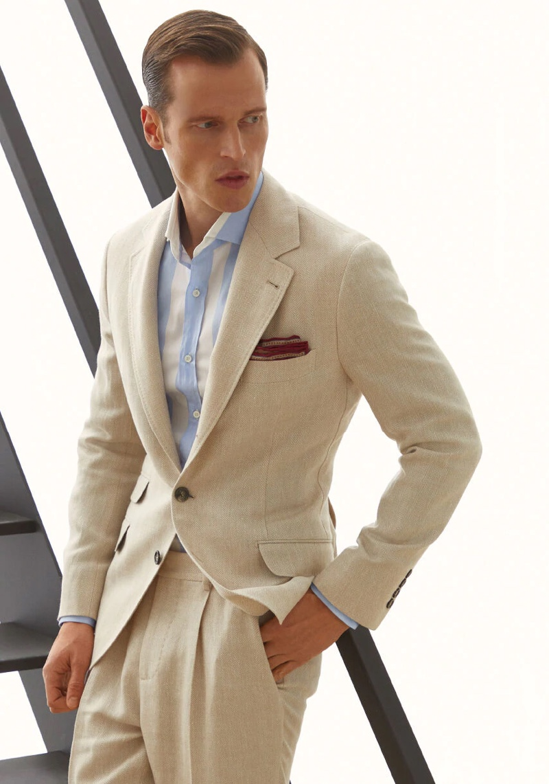 Front and center, Lars Burmeister dons a Brunello Cucinelli linen, wool, and silk chevron deconstructed suit.