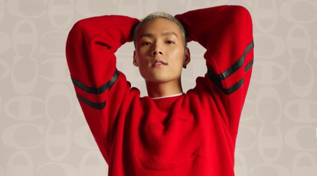 Jeffrey Tung sports a red pullover and black joggers from the Coach x Champion collection.