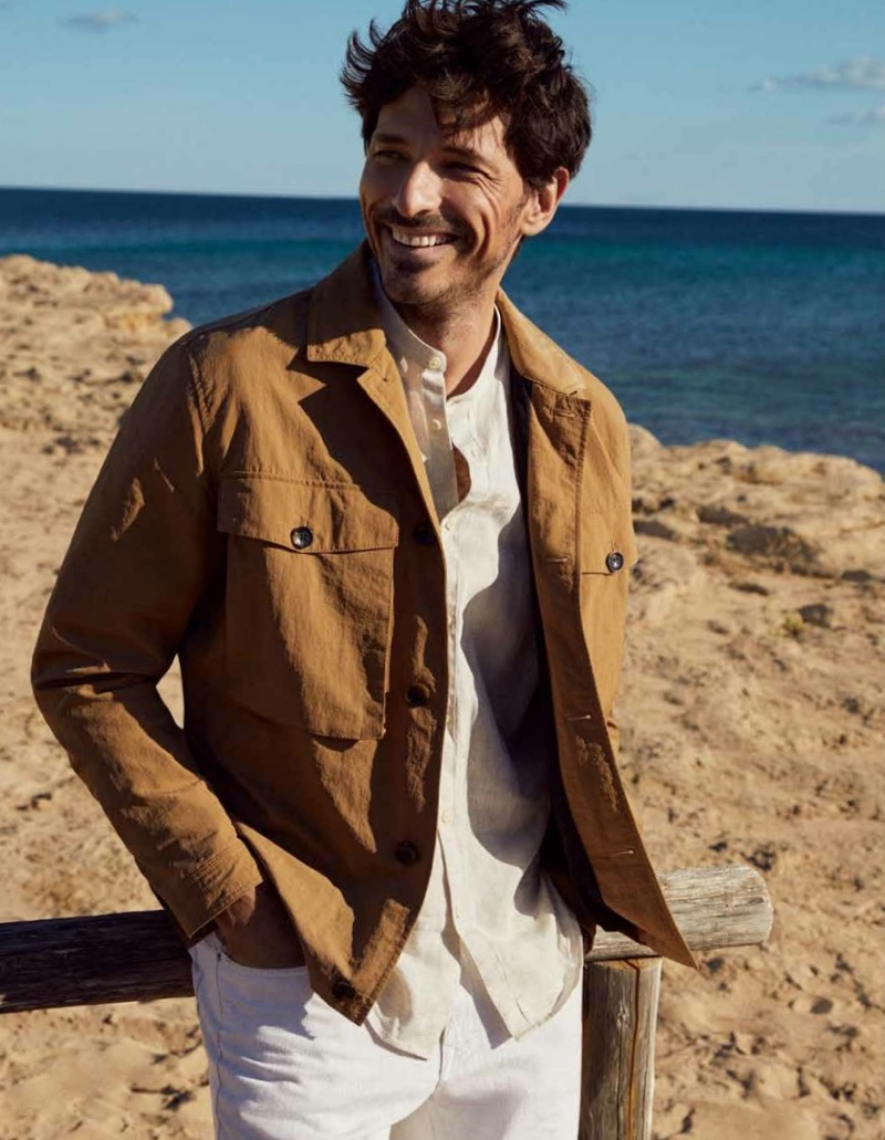 All smiles, Andres Velencoso wears a linen jacket and shirt with white jeans from Esprit's spring-summer 2021 men's collection.