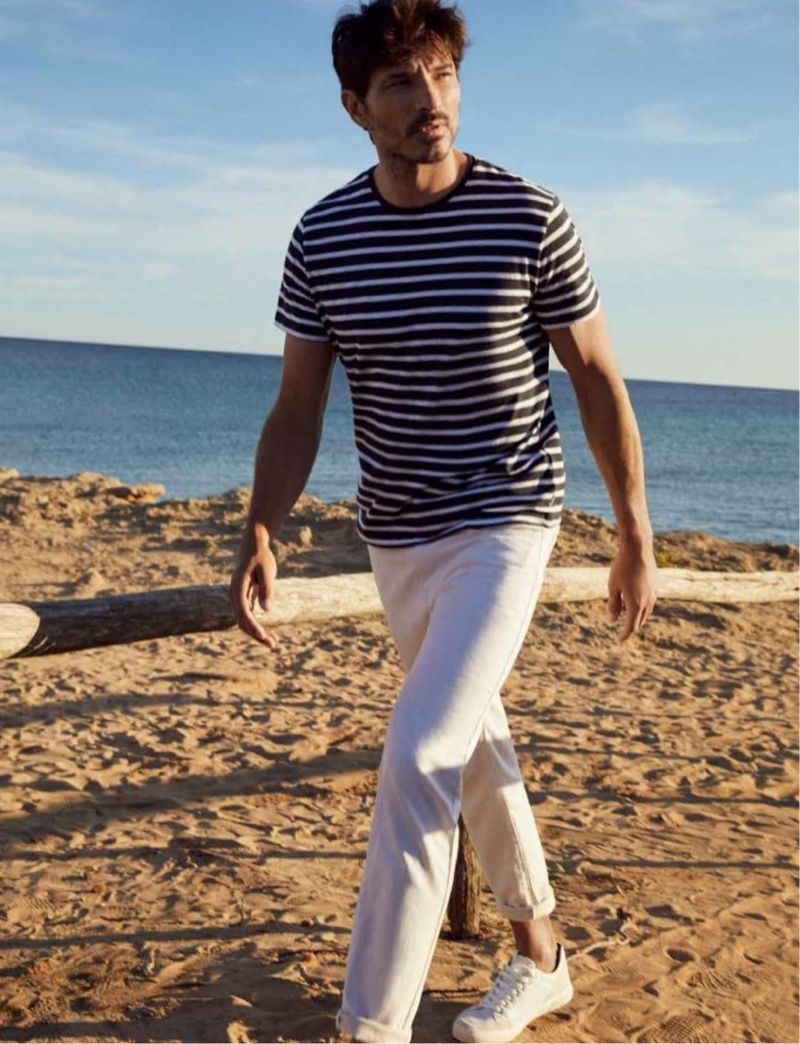 Hitting the beach, Andres Velencoso rocks a striped tee with white jeans from Esprit's spring-summer 2021 men's collection.