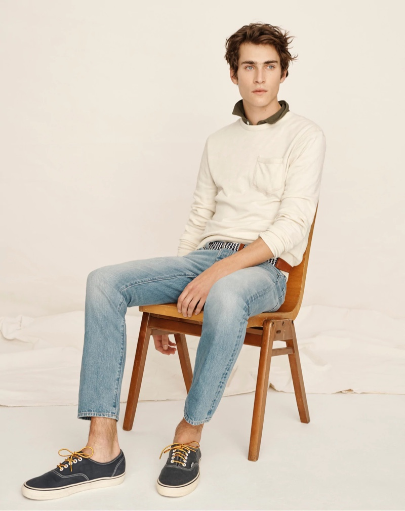 Liam Kelly models a lightweight sun-faded french terry sweatshirt with light wash denim jeans by J.Crew.