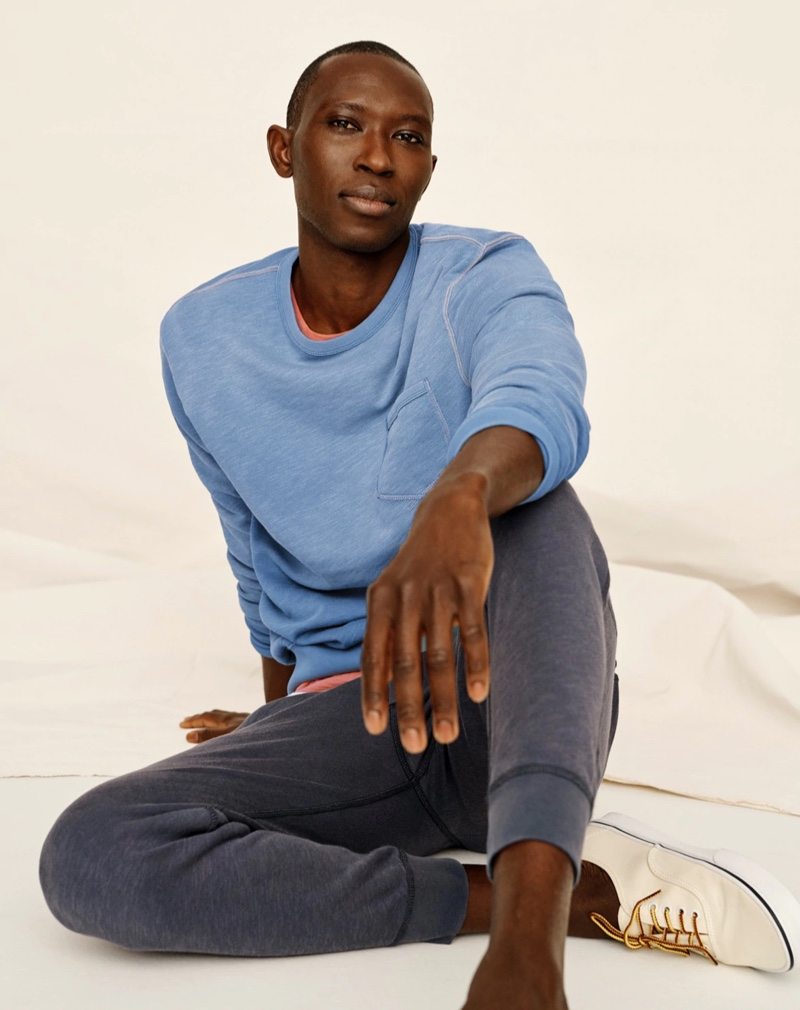 Relaxing, Armando Cabral sports a lightweight sun-faded french terry sweatshirt and jogger sweatpants from J.Crew.