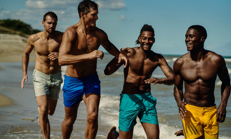 Models Andrew Cooper, Ollie Edwards, Ty Ogunkoya, and James Kakonge sport swimwear from Orlebar Brown's Atlantic collection.