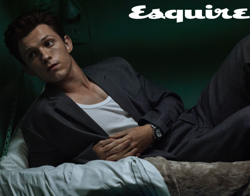 Lounging, Tom Holland dons a Prada suit, Hanes tank, and Rolex watch for Esquire.