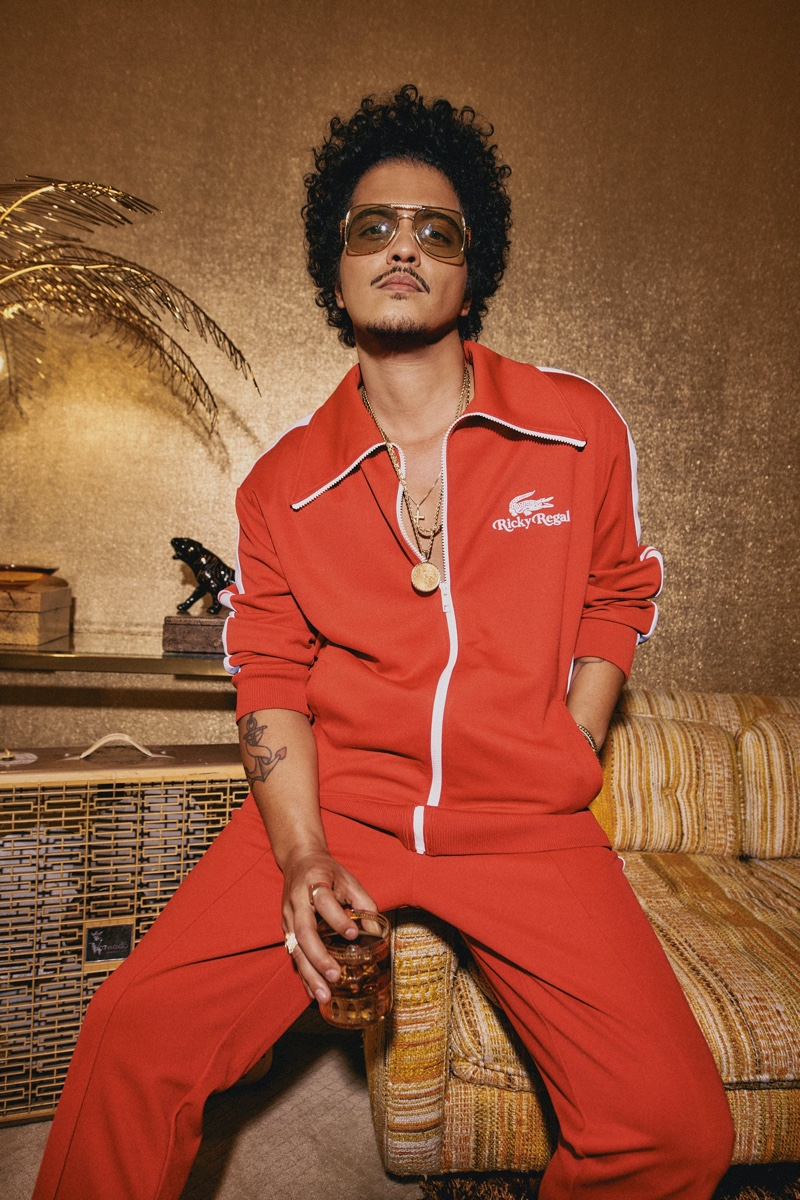 Front and center, Bruno Mars rocks a red tracksuit from his Lacoste Ricky Regal collection.