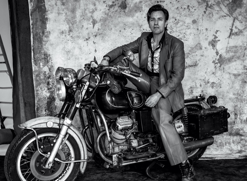 Posing on a motorcycle, Ewan McGregor dons a Gucci suit for his VMAN cover photoshoot.