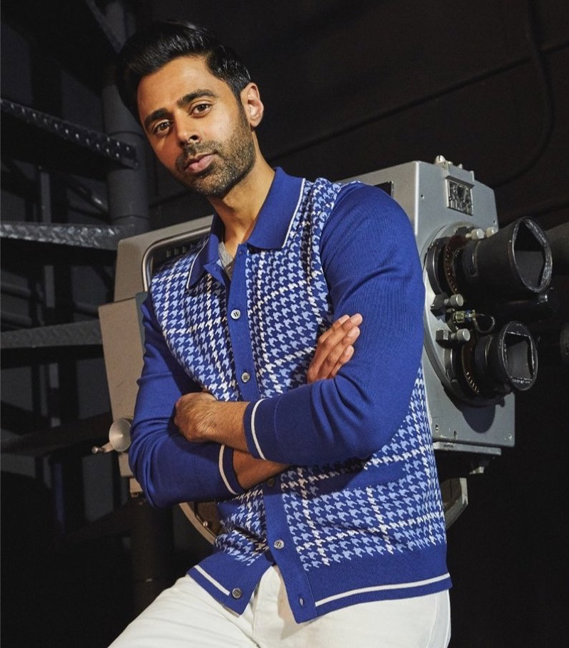 Front and center, Hasan Minhaj dons a Todd Snyder long sleeve houndstooth plaid polo and white slim fit Japanese selvedge stretch jeans.