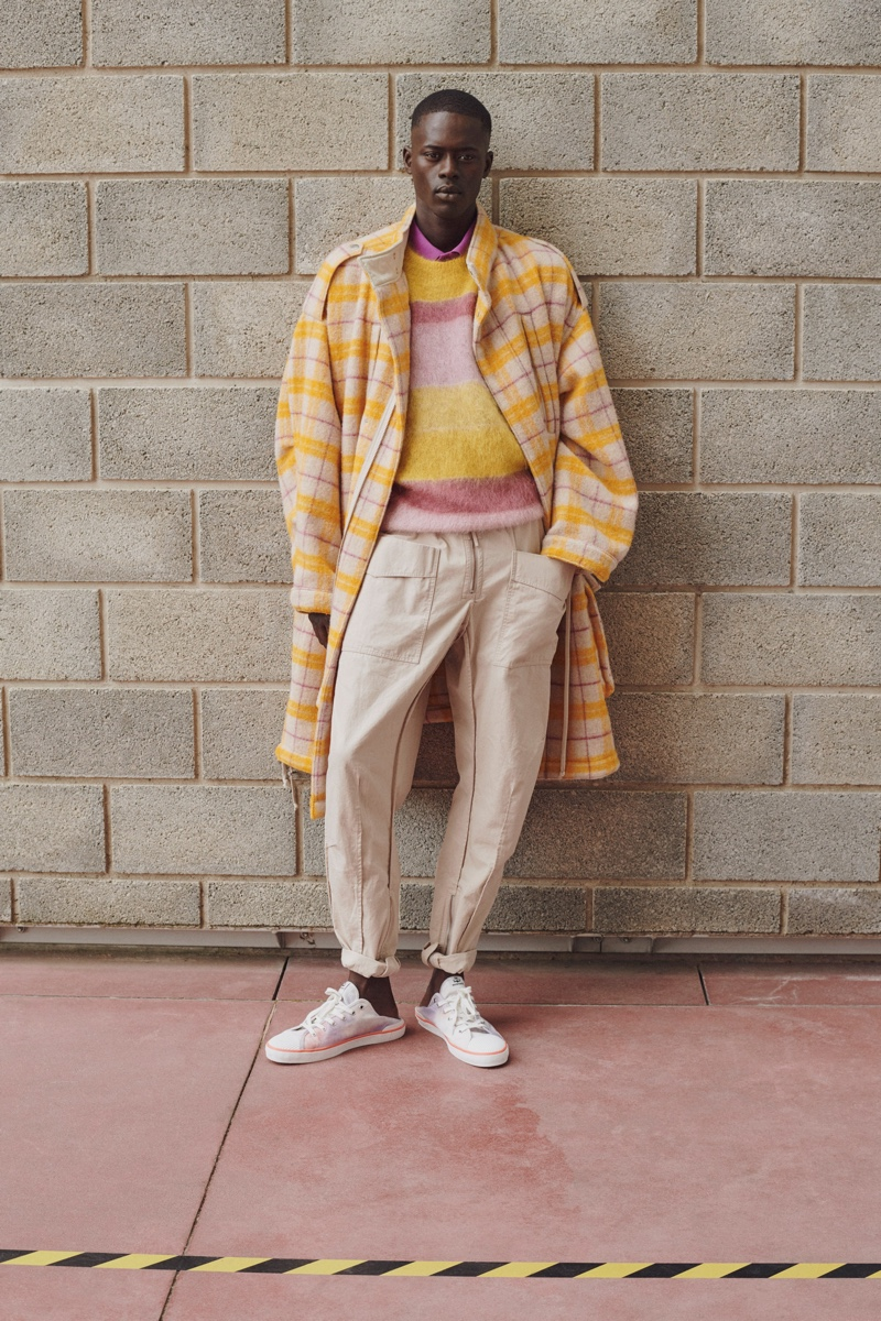 Front and center, Alpha Dia makes a statement in a splash of yellow with a check coat from Isabel Marant's spring-summer 2021 men's collection.