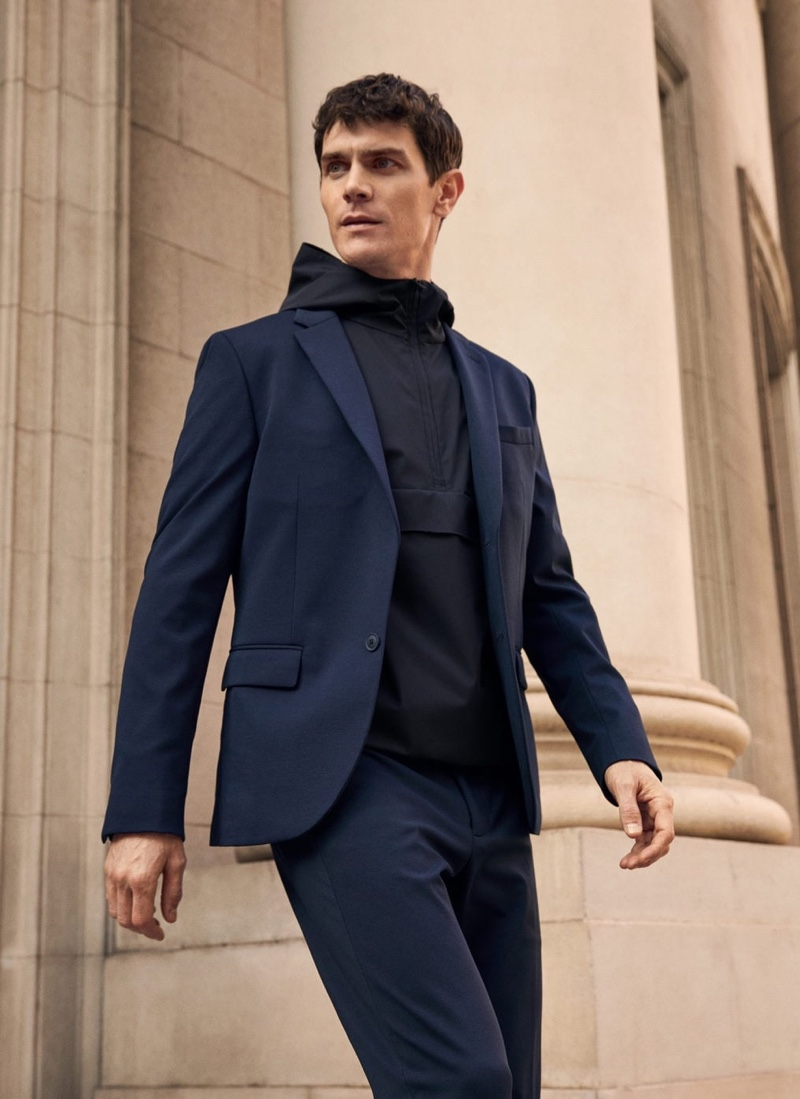 Embracing a navy and black look from Mango's High-Performance collection, Vincent Lacrocq wears a combined knitted sweatshirt with a suit.