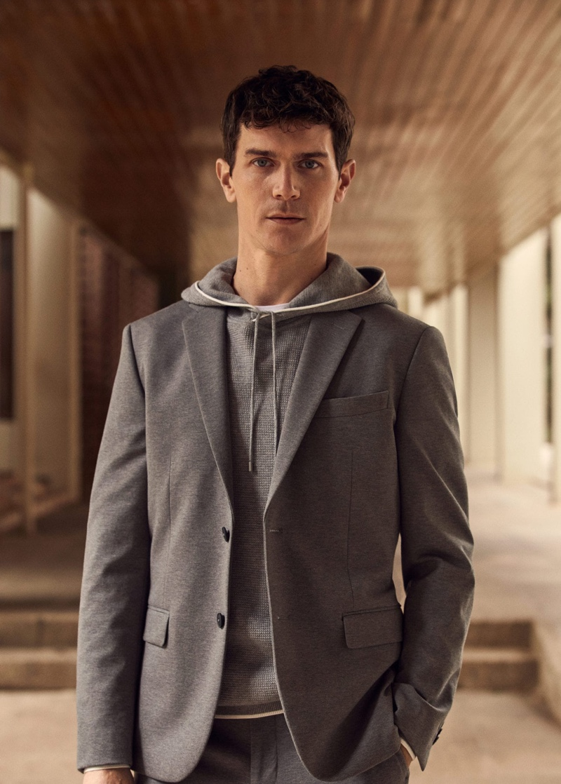 Donning shades of gray, Vincent Lacrocq rocks a slim-fit technical suit blazer with a cotton-blend knit sweatshirt from Mango's High-Performance collection.