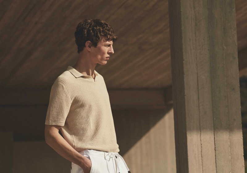 Delivering a side profile, Tim Schuhmacher inspires in a sleek v-neck polo sweater from Massimo Dutti's spring 2021 Limited Edition collection.