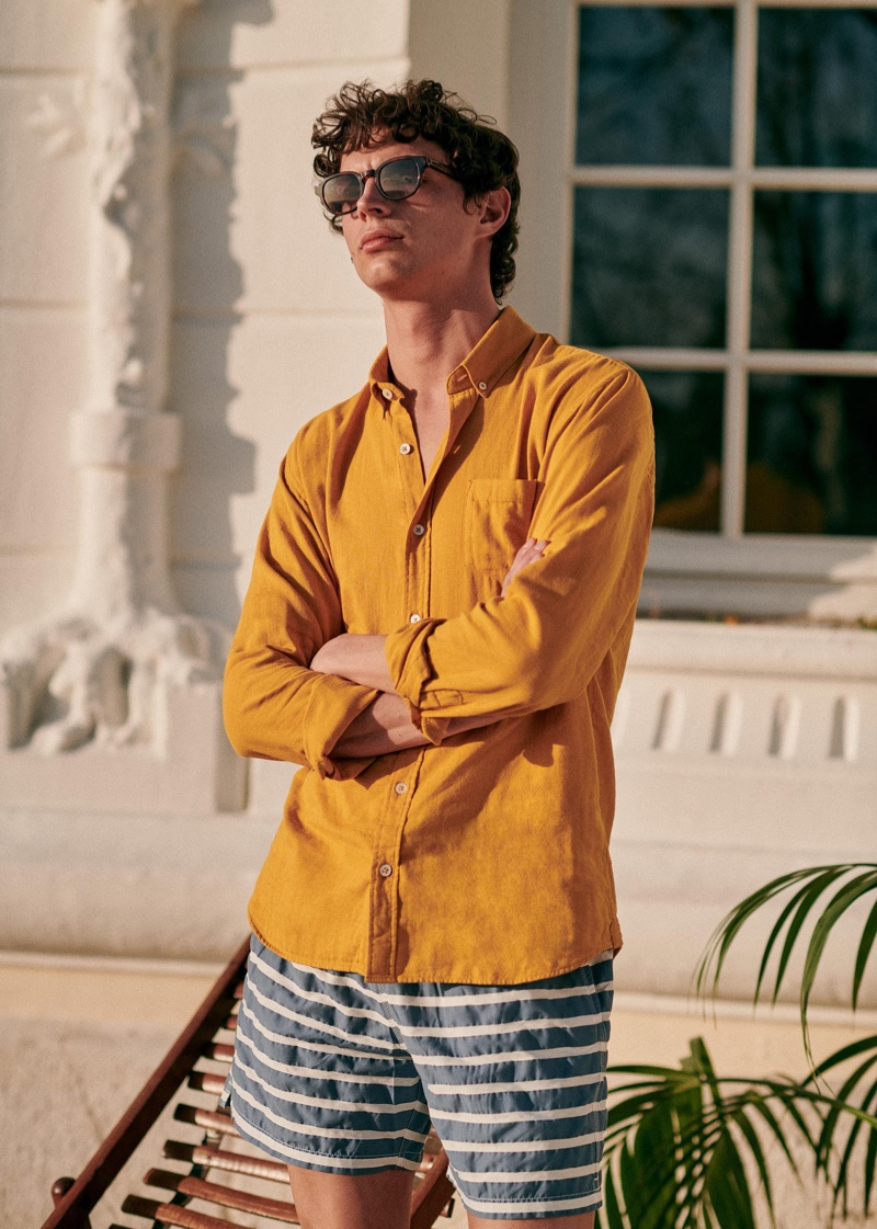 Dressing for warm weather, Andrea Quaranta models a mustard yellow shirt with striped swim shorts and stylish sunglasses by Octobre.