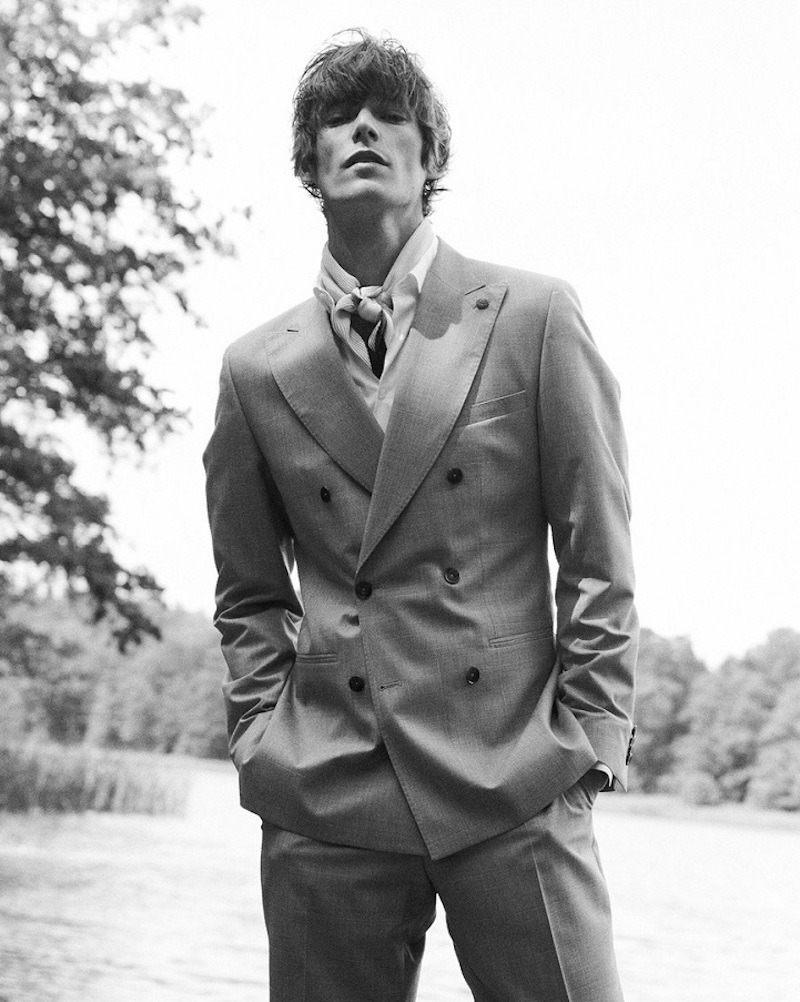 Appearing in a black and white photo, Conrad Leadley models a sharply tailored double-breasted suit by Club of Gents.