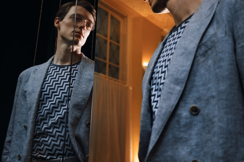 Posing in front of a mirror, Tommaso de Benedictis wears a Giorgio Armani double-breasted mélange linen suit jacket and Intarsia silk, cashmere, and linen-blend sweater from Mr Porter.