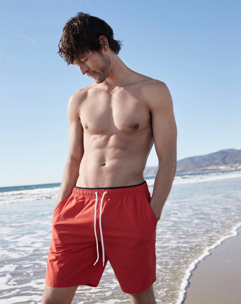 """Hitting the beach, Josh Upshaw sports a pair of J.Crew's 8"""" stretch swim trunks in red coral."""