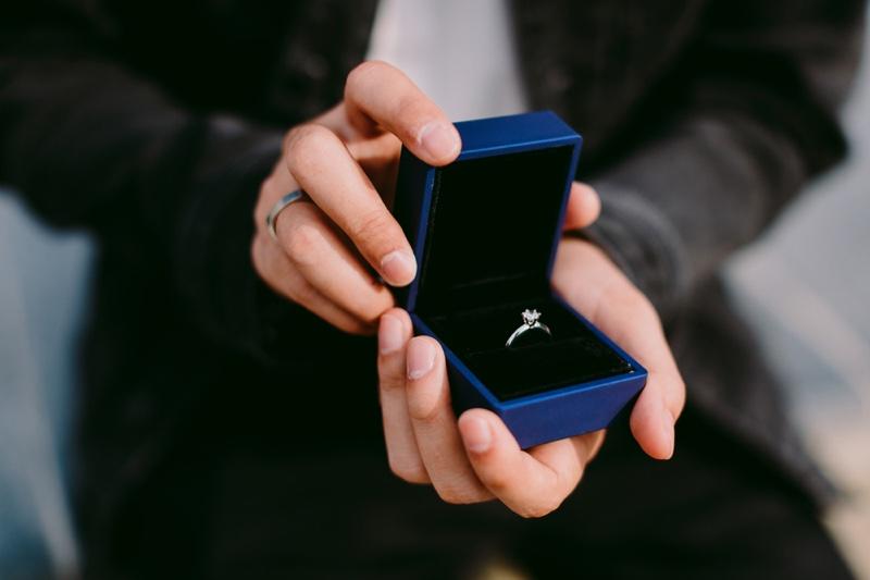 Man Holding Blue Engagement Ring Box